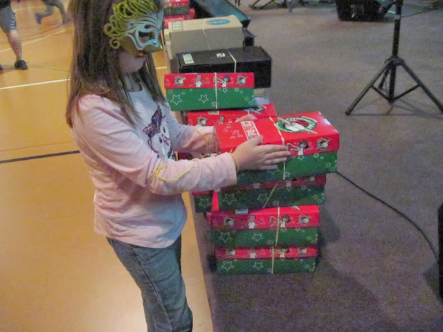 Little girl with Operation Christmas Child shoeboxes at packing party.