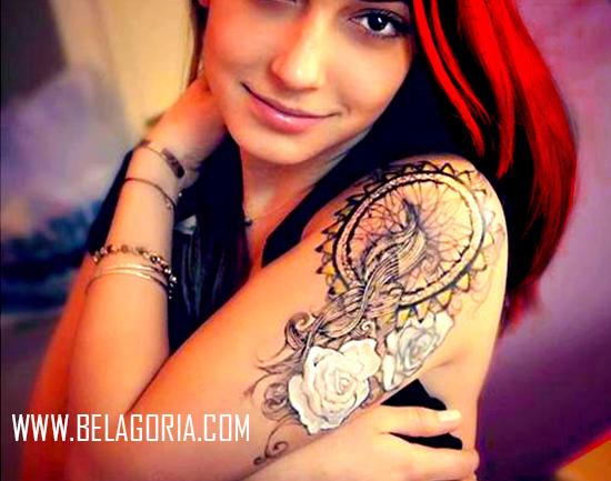 Una preciosa mujer gitana de pelo rojo nos mira, lleva en su brazo izquierdo un tatuaje de atrapasueños