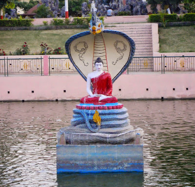 Buddha in the coils of the Mucalinda serpent, in the center of a lake in Bodh Gaya.