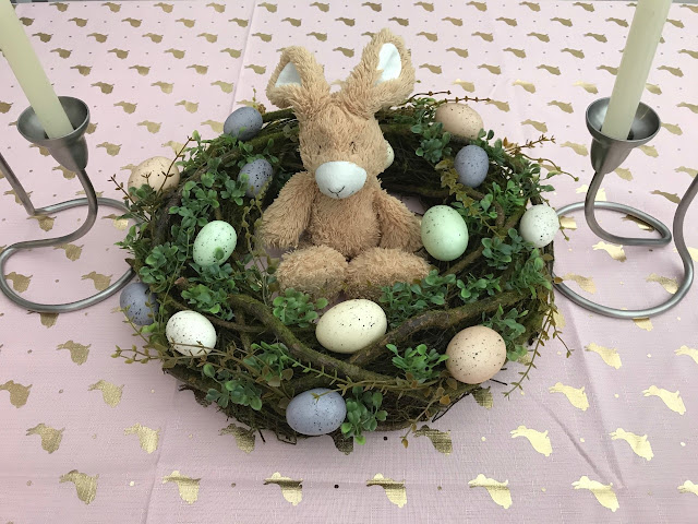 Pale pink tablecloth with gold bunnies printed on it, with candlesticks either side of an easter wreath with pastel coloured eggs with a cuddly bunny sitting in its centre