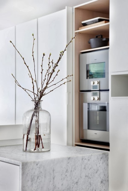 Clean lines and white and bright surfaces in marble, corian and wood create a light and airy feeling perfect