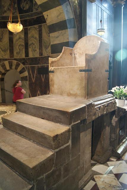 Der Karlsthron. Auf einer steinernen Empore steht ein Thron aus Stein.