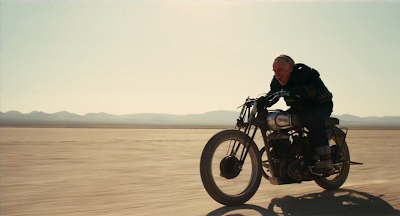 Philip Seymour Hoffman as Lancaster Dodd in The Master, rides a bike in the desert, directed by Paul Thomas Anderson