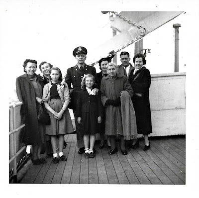 "Natalie Vasilev, Lana Thomson, Tanya Sarsfield, Captain Robert ""Bobby"" Ford, Lena Vasilev, Stephany Mitrofanenko, Mrs. Triantafillidis, and Ann and Bill Schwarz on board the SS Pacific Transport in January 1953"