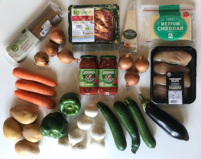 a flat lay of products received in exchange for the post including: chicken breast fillets, cheddar, parmiagiano, beef mince, spaghetti, onions, carrots, potatoes, peppers, mushrooms, courgettes and an aubergine