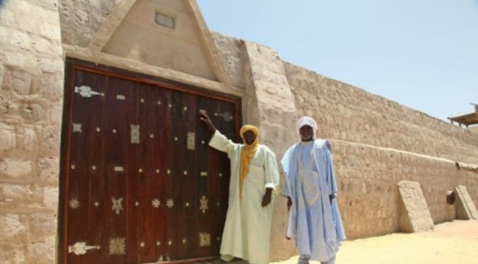 """Workers pose in front of newly unveiled Sidi Yahia mosque doors on September 19, 2016, which were destroyed during a spree of destruction in 2012 by Al-Qaeda-linked Ansar Dine. By Sebastien Rieussec (AFP). Timbuktu (Mali) (AFP) - The doors of a revered 15th-century mosque hacked apart by jihadists in Mali's ancient city of Timbuktu four years ago were unveiled on Monday restored to their former glory.  The """"secret door"""" of the Sidi Yahia mosque in the fabled caravan city fell victim to a spree of destruction in 2012 by Al-Qaeda-linked Ansar Dine, one of several radical Islamist groups which seized key northern cities that year.  Around 100 Malian political and religious leaders, diplomats and representatives from world heritage body UNESCO gathered for a ceremony, held with a heavy security presence, an AFP journalist at the scene reported.  """"This is a very important day,"""" said the mosque's imam, Alphadi Wandara. """"Since (the days) of our forefathers, for centuries the door has been like that: closed.""""  Muslim prayers were recited for the mosque, which has been on UNESCO's list of world heritage sites since 1988."""