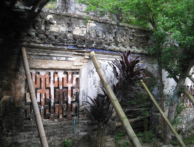 Tường hành lang đi vào hậu cung đã nghiêng, đổ, bà con phải dùng cây để chống.