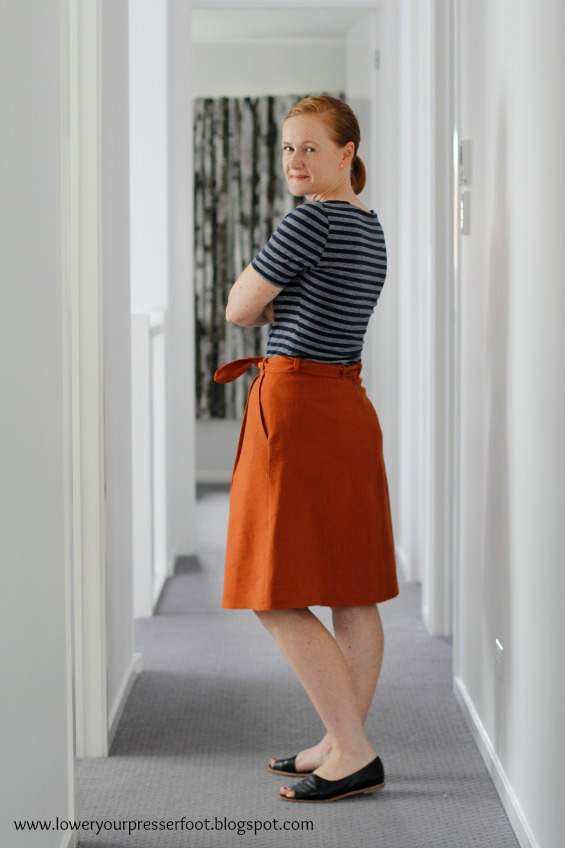 lady wearing a rust coloured pleated skirt with blue and white stripe tshirt