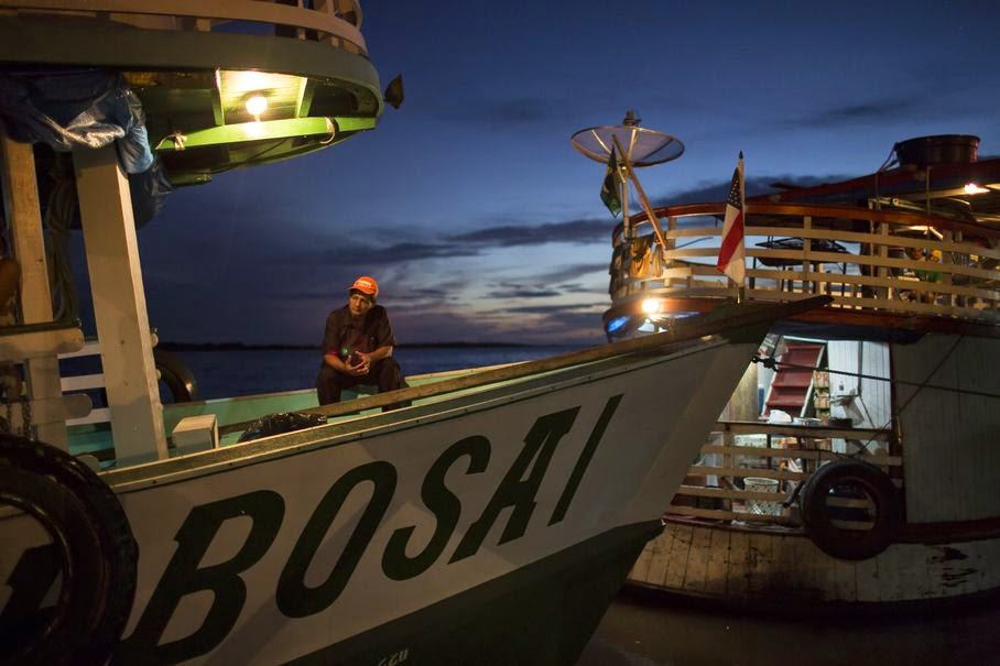 "In this May 22, 2014, photo, a man sits on the ""Almirante Barbosa"" during a quick stop at the port of Manacapuru, near Manaus, Brazil. Boats like the Almirante Barbosa are the lifeline of Brazil's Amazon region, where they transport passengers and staples ranging from rice to diapers, and deliver them to remote riverside villages inaccessible any other way."