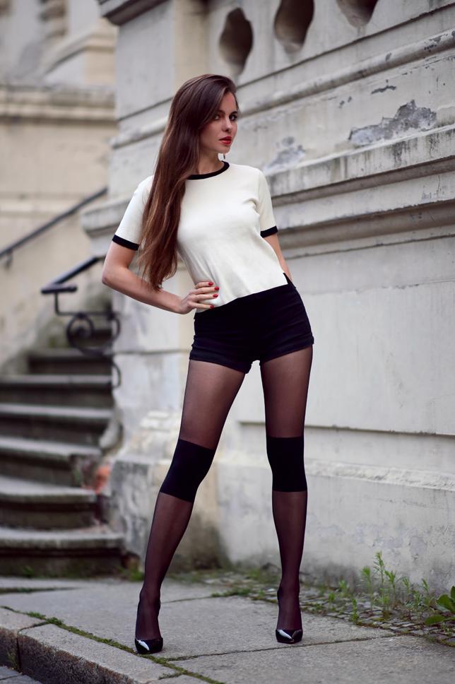 Biały sweterek, czarne szorty, rajstopy z oryginalnym wzorem oraz lakierowane szpilki
