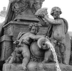 Las figuras de dos niños tras el carro de la diosa. Uno se apoya en el cántaro del que sale agua y el otro alza una caracola.