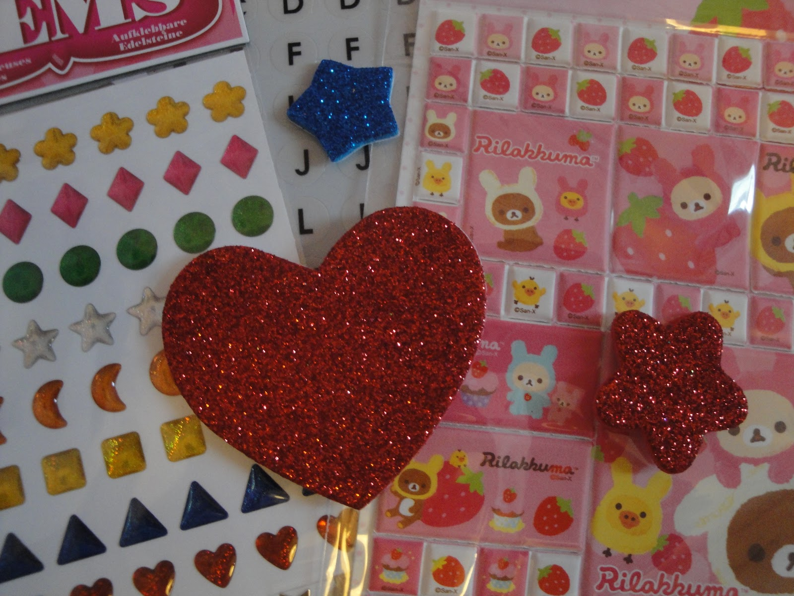 A close shot of a collection of stickers (heart-shaped, stick-on gems, and Rilakkuma stickers).