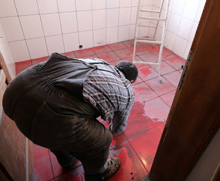 Bekir cleaning the grout off the tiles