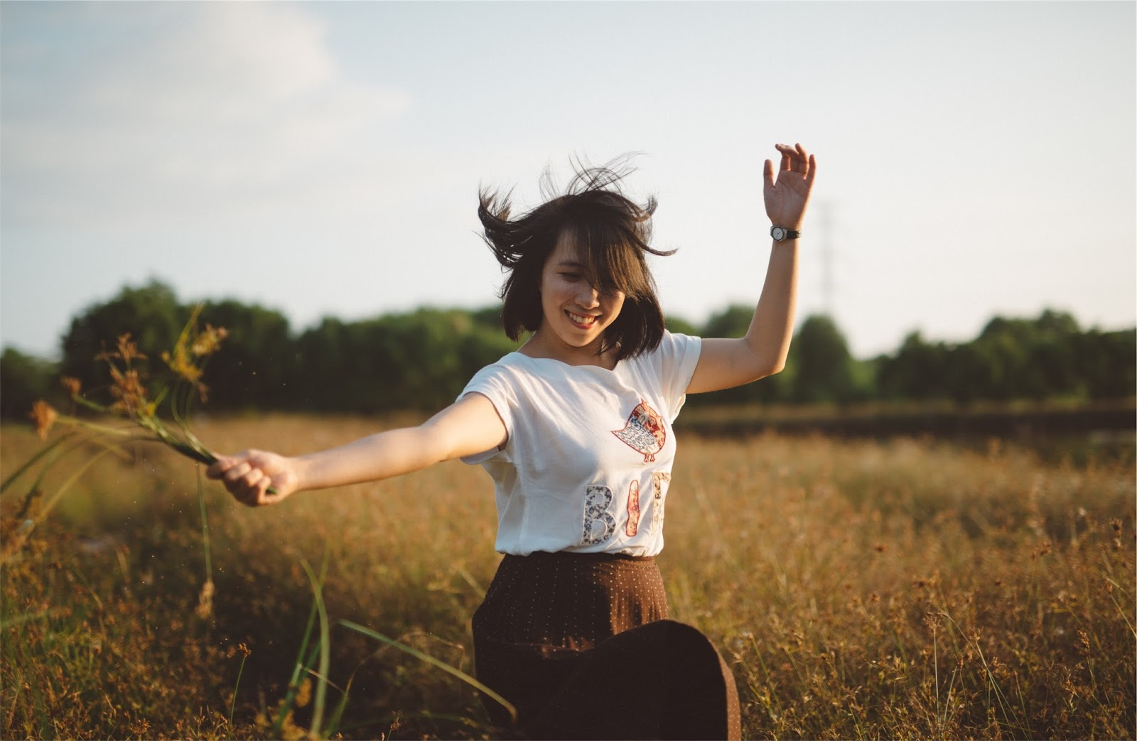 Woman dancing through a field - 20 easy ways to recharge your batteries - stress management - motherdistracted.co.uk