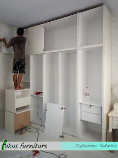 proses pemasangan lemari di lokasi
