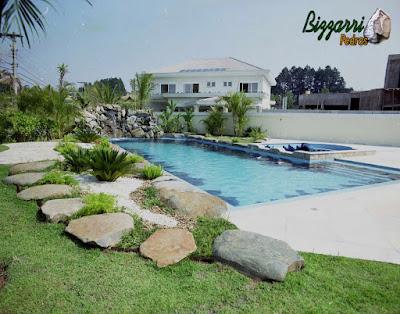 Construção da cascata de pedra na piscina com pedras ornamentais com a execução do paisagismo.