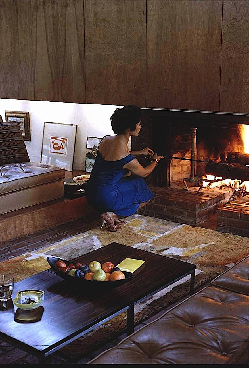 a 1958 Ulrich Franzen interior design photograph, woman in blue stoking fireplace