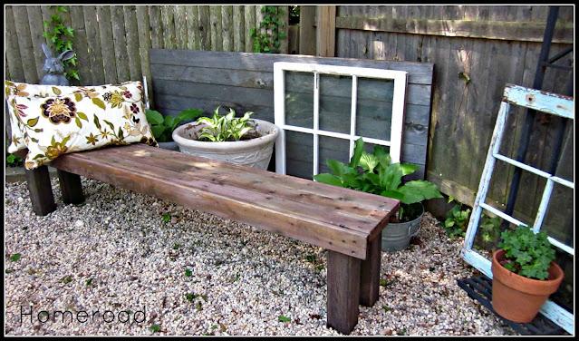 Outdoor bench with pillows in a pea gravel garden