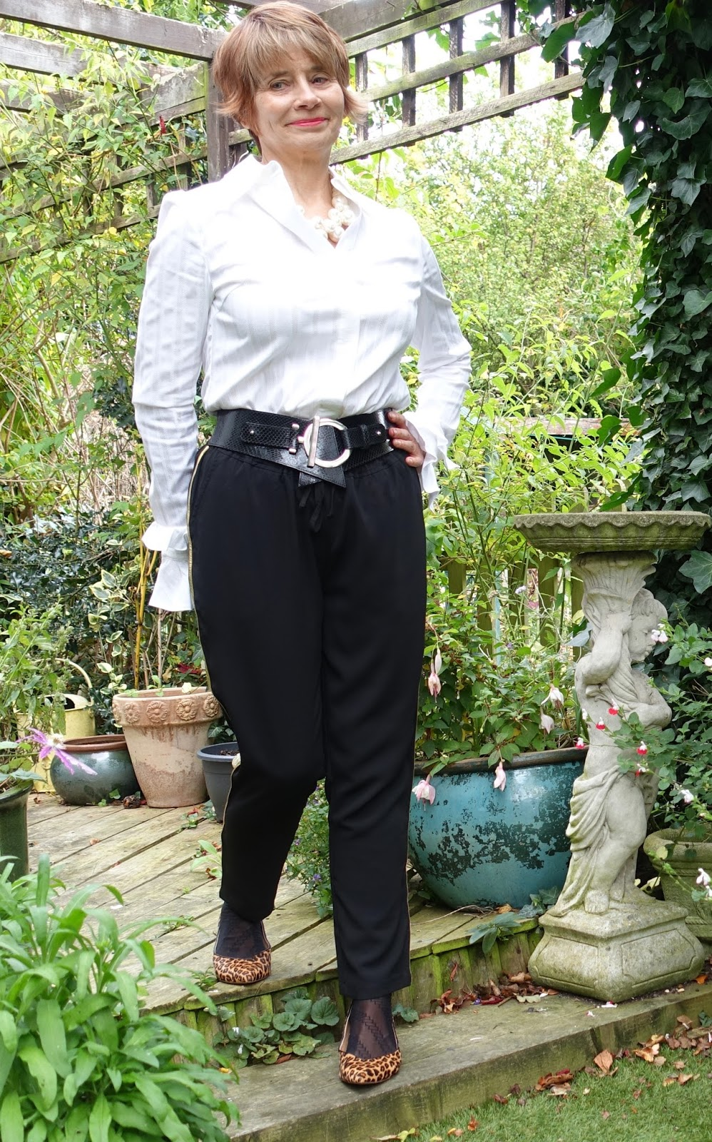 Image showing woman in her 50s wearing gold side stripe trousers , leather waist belt and frilled sleeve white shirt