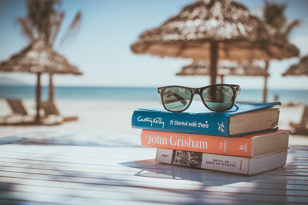 Γυαλιά ηλίου και βιβλία σε παραλία με ομπρέλες