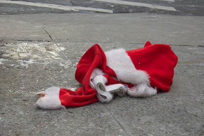 """Cette image montre un amas de tissu rouge et blanc sur un sol gris que l'on imagine être un trottoir. On distingue clairement dans ce tissu en boule et chiffonné un costume de Pere noel, surtour grâce au bonnet qui est identifiable sur la droite. L'element manquant dans cette photo est bien evidemment le Pere Noel lui-meme dont il ne reste nulle trace sinon ce pitoyable costume pose a meme le sol gris et sale. Cette image accompagne le poeme """"Noels immemoriaux"""" du Marginal Magnifique, poeme de circonstances en cette periode de noel. Dans ce brillant texte desabuse Le Marginal Magnifique exprime le profond sentiment de nostalgie qui sempare de l'adulte en cette periode s'il essaie de se rememorer ses sensations d'enfant à l'approche de Noel, sensations intenses et pures qui ne seront jamais egalees dans sa vie future. Pou illusrter ce message, le poeme se termine sur une allusion a la mesavanture du patron du FMI DSK, qui a cree le scandale apres qu'une femme de chambre a porte plainte contre lui pour viol dans un hotel de luxe new-yorkais. Encore un brillant poeme du Marginal Magnifique, à la fois profond, emouvant et drôle !"""