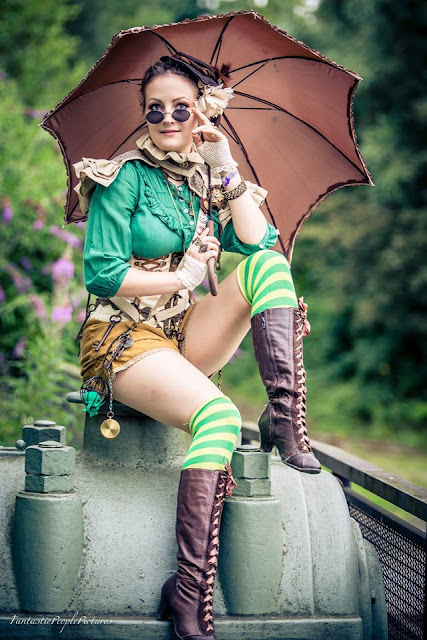A colorful steampunk costume. Green blouse, corset, shorts, boots and parasol.