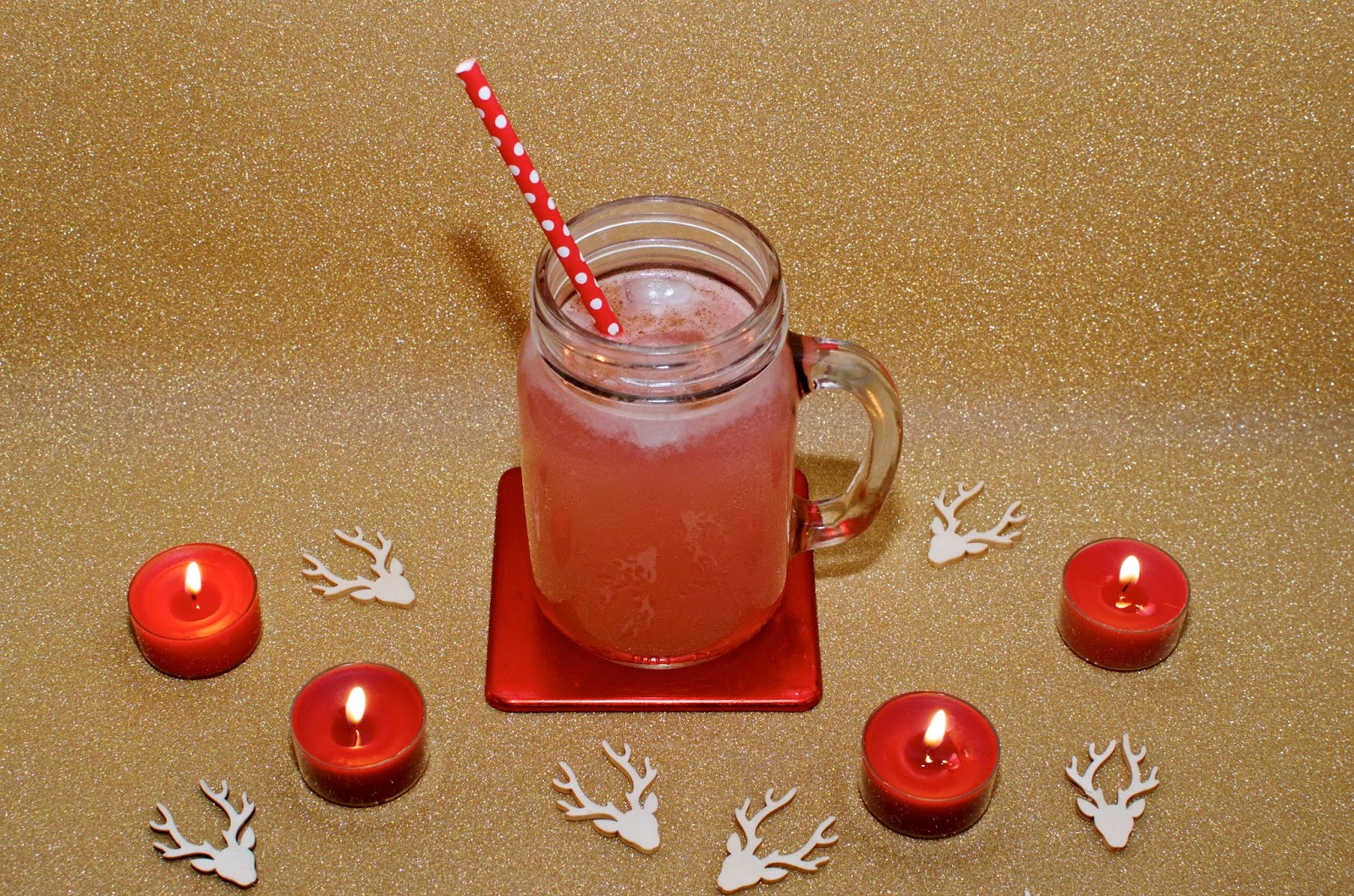 pink cocktail, red polka dot straw, red candles and reindeer confetti