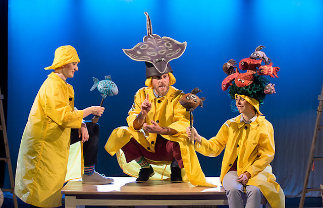 Three people dressed in yellow fisherman clothing with little fish props.