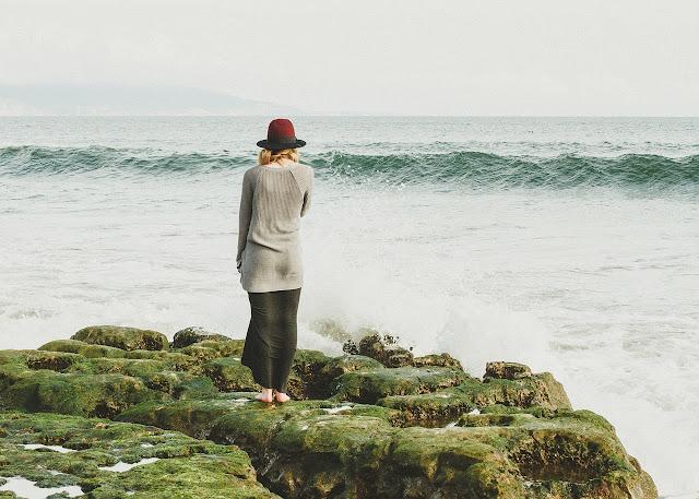 Fille seul au bord de l'eau - Debout sur des pierres entassées