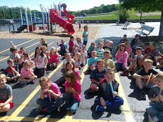First grade students sitting on the playground Indian style posing for a picutre
