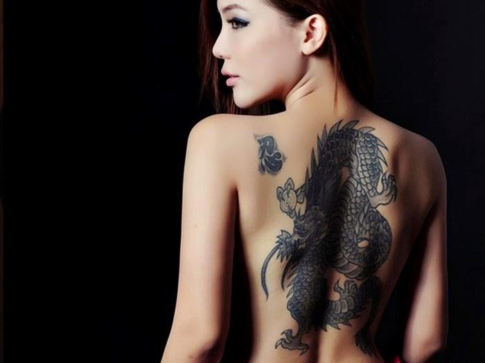 Chica asiatica de espaldas lleva un tatuaje de dragon tibetano