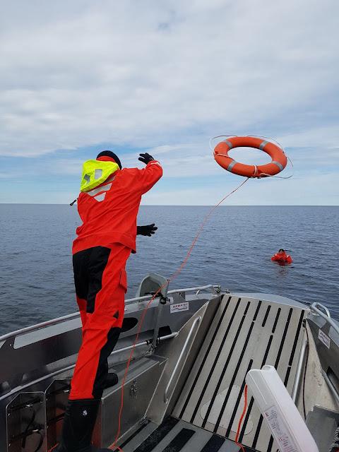 Pelastautumispukuinen henkilö heittää pelastusrengasta meressä kelluvalle henkilölle veneestä
