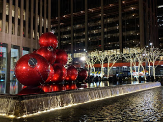 Giant red Christmas ball ornaments stacked above a fountain, trees wrapped in white lights, near Rockefeller Center, New York, New York