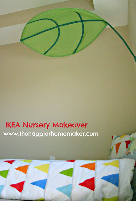 A fabric, green leaf over a twin bed in a nursery