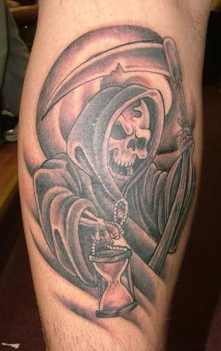 Uma sorridente Grim Reaper tatuagem. O reaper é visto estar segurando um copo de hora como se deliciosamente contar o tempo restante de uma alma, na terra dos vivos.