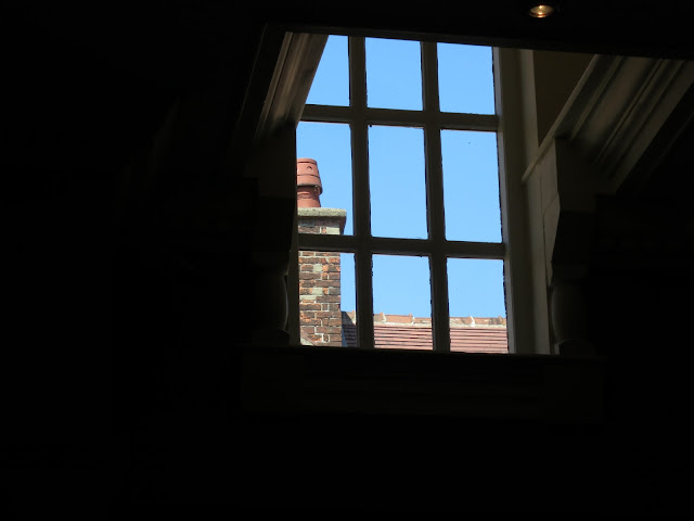 Looking through window with nine panes at chimney and red tiled roof beyond.