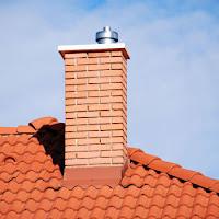 Kiremitli bir çatıda tuğla ile örülmüş bir baca