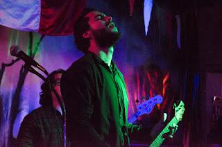 lider de banda durante una presentación en un bar mientras siente mucho una canción