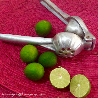 Several Whole Limes And Some Cut In Half With A Metal Lime Squeezer On A Fuschia Pink Table Mat