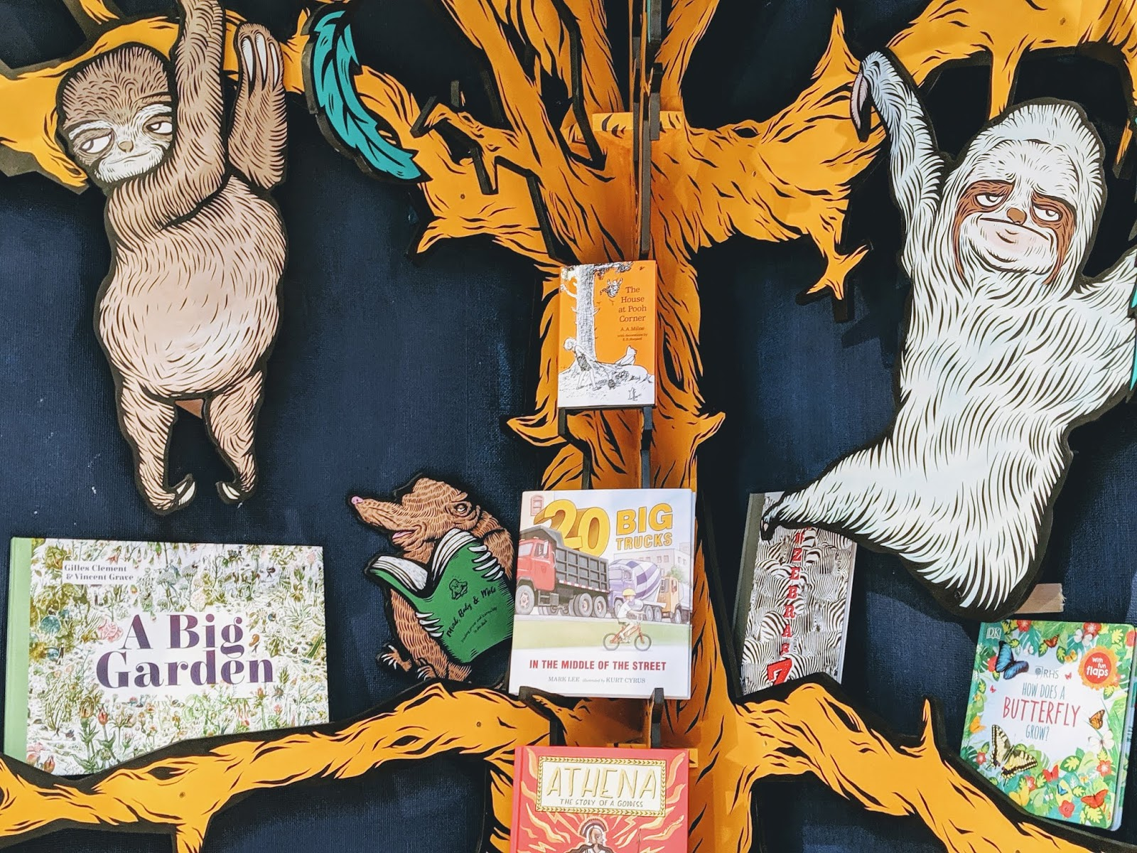 Cartoon sloths hanging in a tree with books in Mr B's children's section