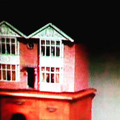 Screen shot of a vintage dolls house in the 1970s TV programme Sapphire and Steel.