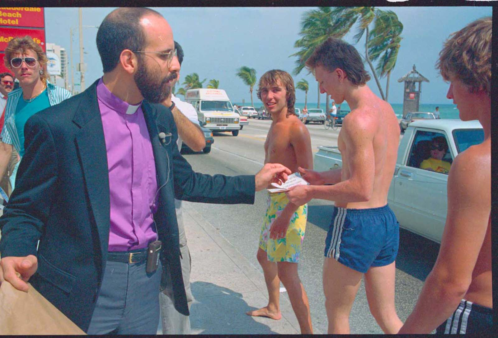 Rev. Fred Tondalo (L) passes out condoms along the highway A1A strip. 1987.