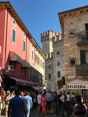 Trange gater med mye folk. Et borgtårn sees i bakgrunnen.