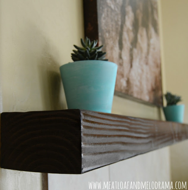 succulents in turquoise pots on wood beam mantel