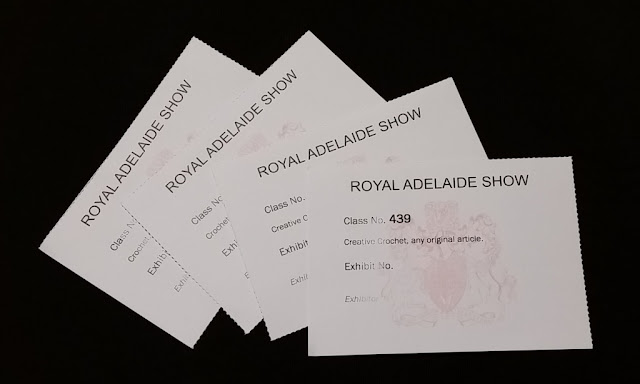 "Four cards fanned out. Each card has the heading ""ROYAL ADELAIDE SHOW"" and is watermarked with the show's coat of arms. Each card has room for the Class no., Exhibit no. and Exhibitor no. The details have been erased for confidentiality."