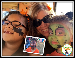 A girl with a bat painted on her cheek, a younger girl with face painting to resemble a witch, and a boy with his face painted to resember a jack o lantern