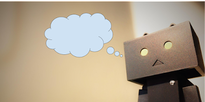image.  Cardboard robot with a blank thought bubble