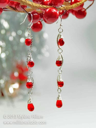 Curved silver bars are linked together with red teardrop crystals to create chain of light earrings.