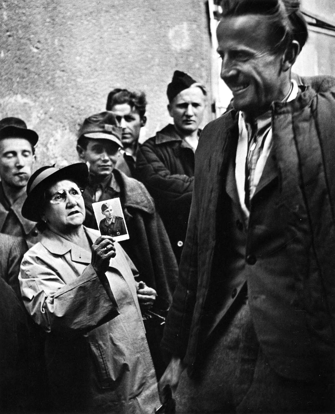 A smiling prisoner of war returning home to Vienna passes a woman holding a photograph up in a mixture of hope and despair.