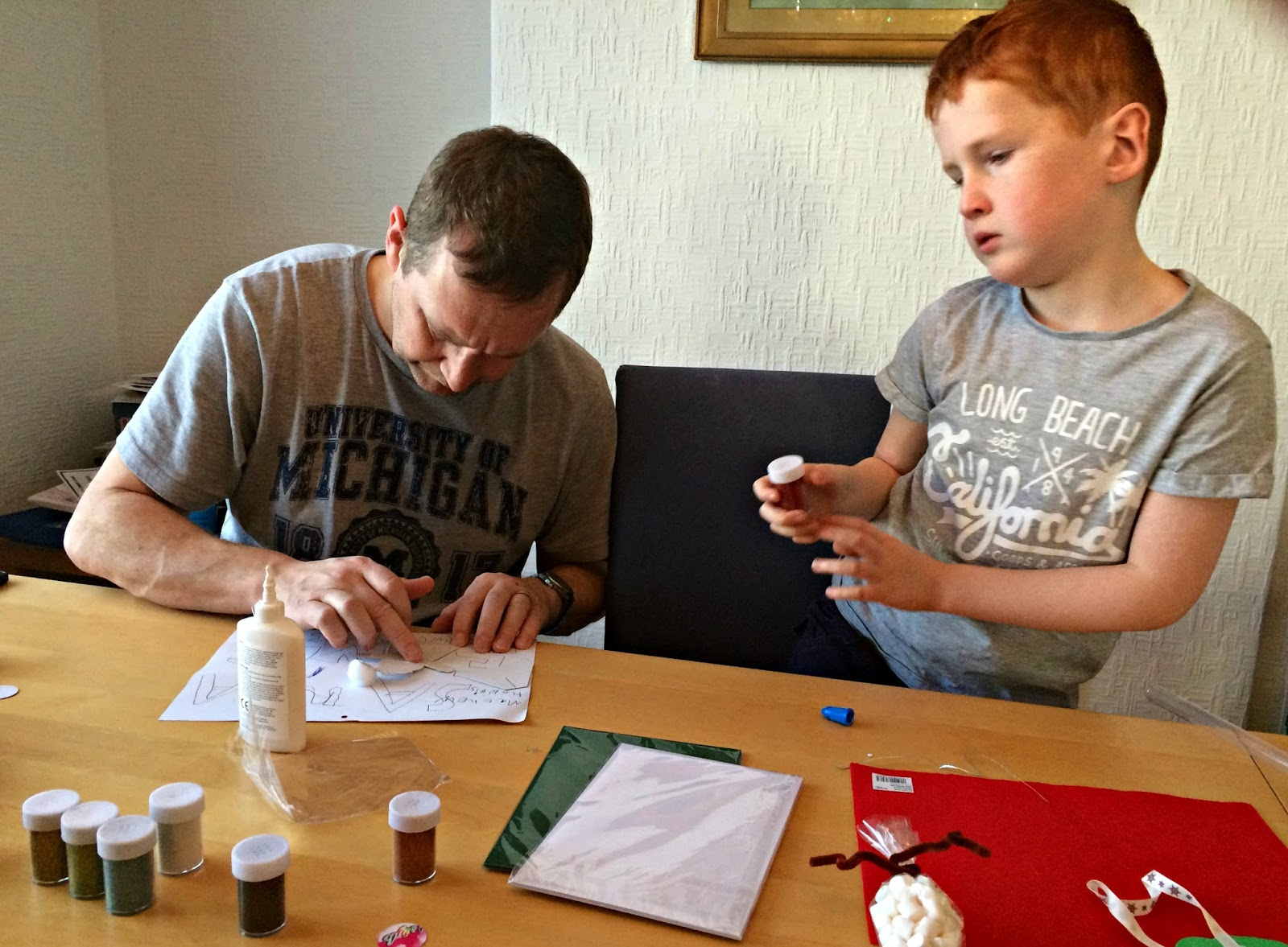 Mat and Ieuan making a Santa Claus on card with glitter